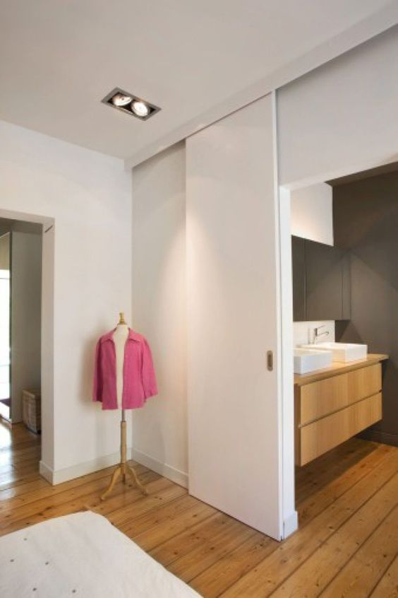 a simple and basic white sliding door separates the bedroom and the bathroom and looks exctly like a wall to match the space