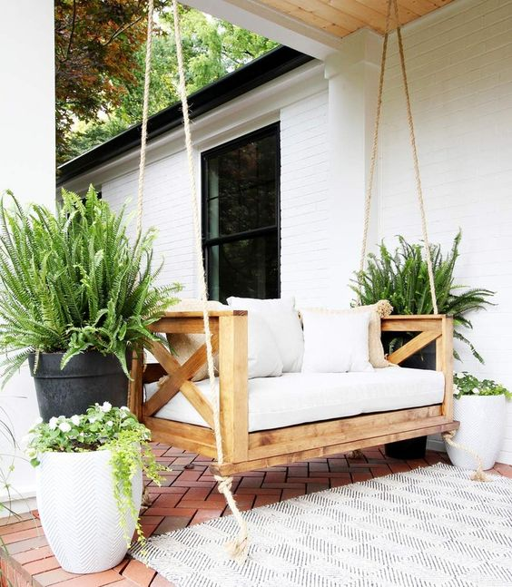 a simple and cute porch space with a hanging daybed of wood, with potted plants and a printed rug is very welcoming
