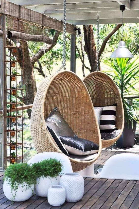 a simple and modern deck with hanging woven egg-shaped chairs, printed pillows, potted greenery, pendant lamps and a side table