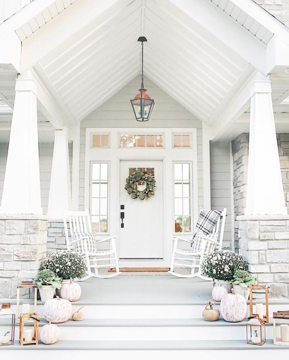 a simple and neutral front porch with white rockers, plaid textiles, potted blooms and greenery and whitewashed pumpkins