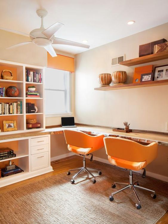 a simple mid-century modern home office with a large built-in storage unit, open shelves, a built-in living edge desk, yellow chairs