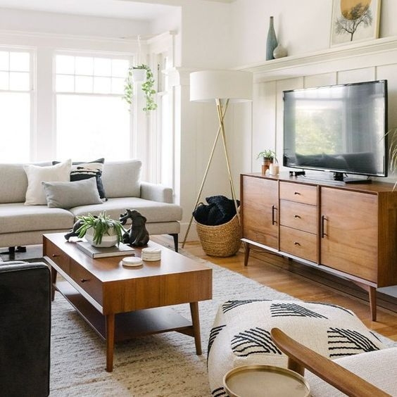 a simple mid-century modern living room with a creamy sofa, a stained TV unit and coffee table, printed pillows and some greenery