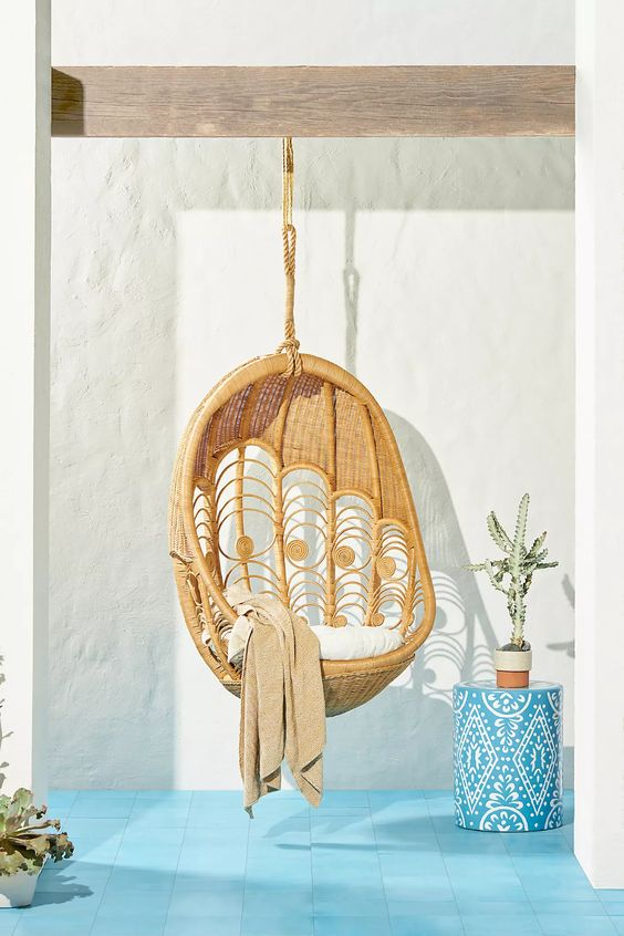 a cozy outdoor nook with a hanging chair