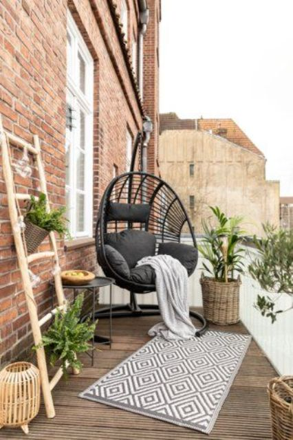 a small and cozy boho balcony with a dark stained deck, a black hanging chair, black and printed textiles, potted plants in baskets and a candle lantern