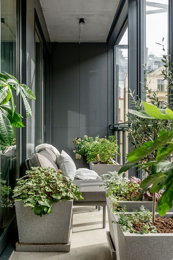 a small and laconic balcony with potted plants, a small grey loveseat and cool views is a lovely space to spend some time and relax