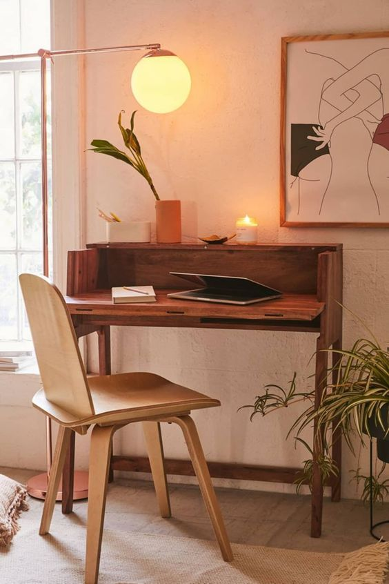 a small and lovely mid-century modern working space with a small stained desk and a plywood chair, a cool artwork and a floor lamp