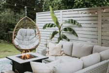 a small and very welcoming space with a white wicker corner sofa, a fire pit, a rattan chair and an umbrella plus a printed rug