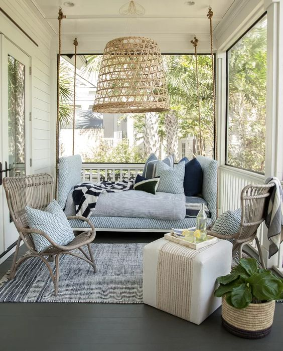a small and welcoming coastal screened porch with rattan chairs, a soft blue sofa, a pouf, a woven pendant lamp and a potted plant