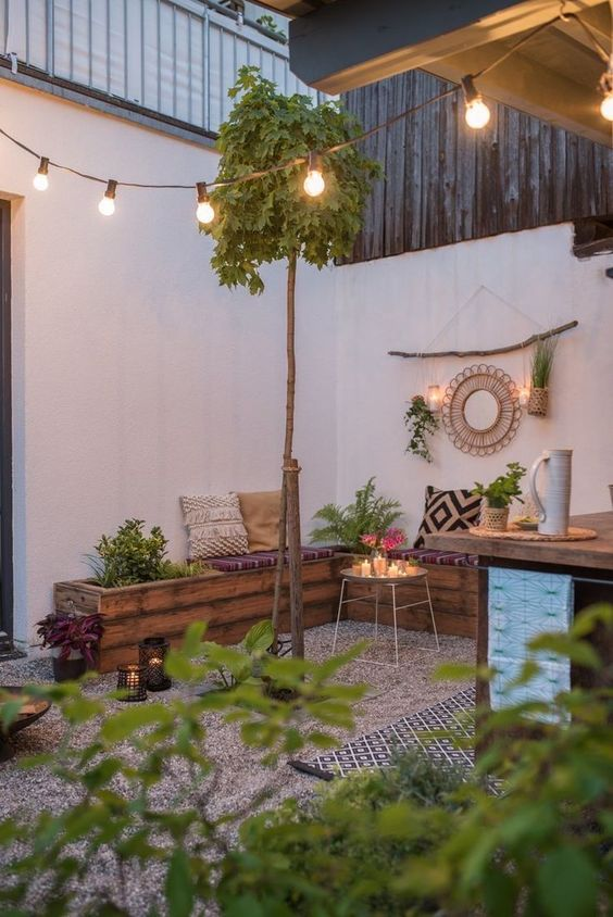 a small and welcoming outdoor space with a gravel floor, a pallet wooden bench, printed pillows and a rug, potted plants and greenery