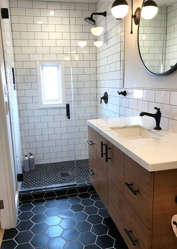 a small mid-century modern bathroom with white subway, black penny and hexagon tiles, a floating vanity, a round mirror and sconces