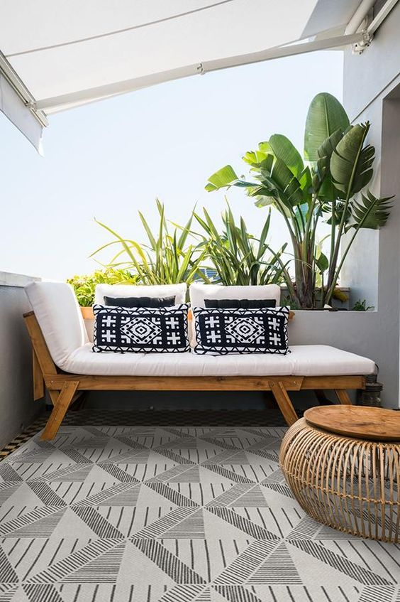 a small modern balcony with a tropical feel, with a lounger and printed pillows, a wooden coffee table and potted plants
