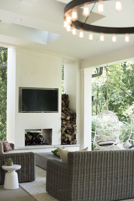 a small modern terrace with a built-in fireplace and a TV, firewood storage, wicker furniture, a low coffee table and a lovely chandelier