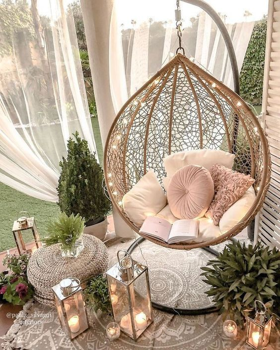 a small outdoor nook with mosquito nets, a hanging rattan chair, lights, candle lanterns and greenery around is a dreamy space to be