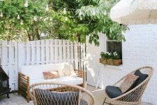 a small outdoor space wiht a wooden sofa, rattan chairs with black upholstery, greenery and string lights over the space
