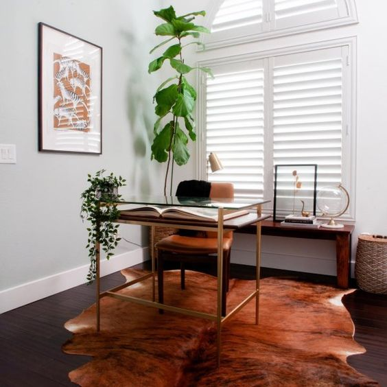 a small working space with a tiered desk, a leather chair, a faux animal skin rug, a console table with some artworks and potted plants