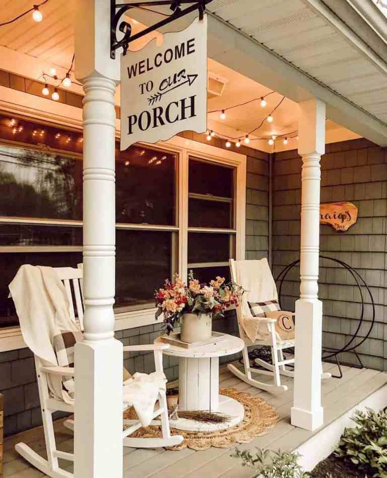 a small yet lovely farmhouse porch with white rockers and a side table, a jute rug, a sign, some string lights and blooms