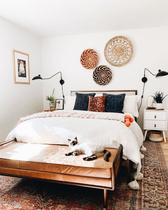 a small yet welcoming mid-century modern bedroom with a wooden bed, an upholstered bench, decorative baskets, printed pillows and an artwork