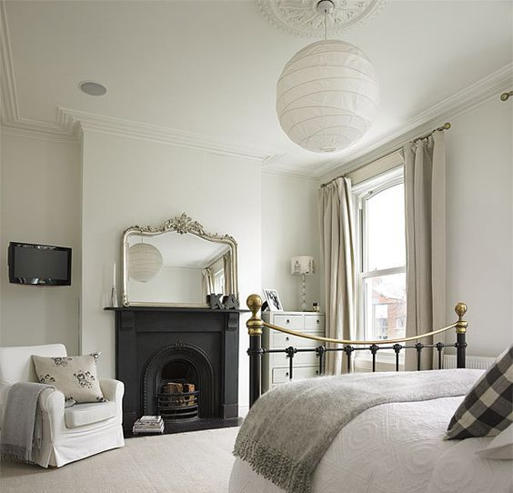 a sophisticated Victorian bedroom in neutral shades, with a metal built-in fireplace, a metal bed, neutral textiles and a grey dresser plus a mirror