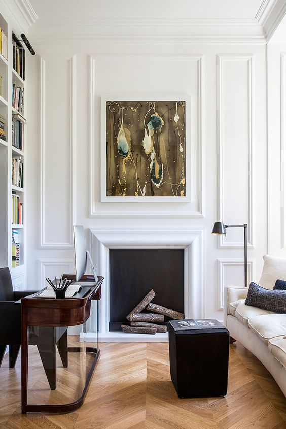 a sophisticated home office with white paneling, a non workign fireplace, a dark stained rounded desk, a black pouf and a creamy sofa is wow