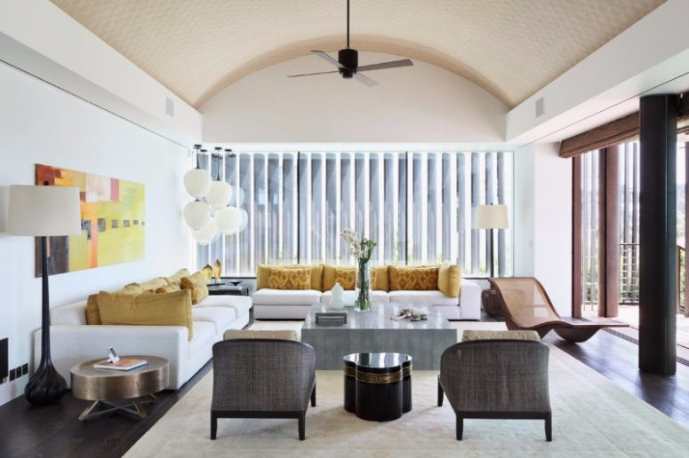 a sophisticated mid-century modern living room with two white sofas, a stone coffee table, grey rattan chairs, a colorful artwork and bright mustard pillows