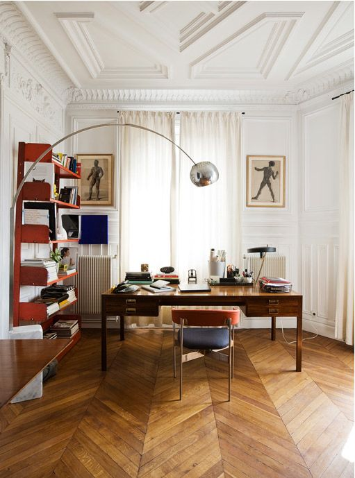 a sophisticated mid-century modern work space with a stained desk, a navy and red chair, red shelves, cool artworks and a floor lamp