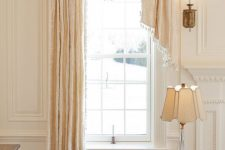 a sophisticated neutral space with a tall and narrow French window with a drapery, neutral furniture and lamps and lights