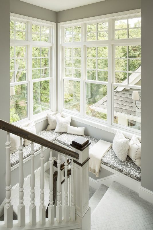 a staircase with cozy nook created around a large corner window, with printed upholstery and neutral pillows is amazing