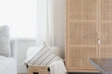 a storage unit with cane doors and a tassel looks very lightweight and ethereal but still gives you enough storage space inside