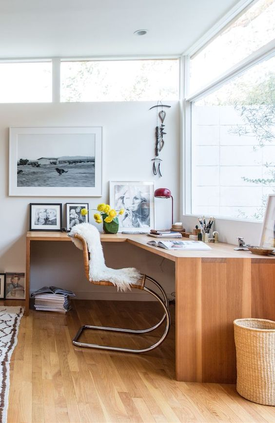 a stylish and light-filled mid-century working space witha  corner desk, some skylights, a rattan chair, cool artworks and a red lamp