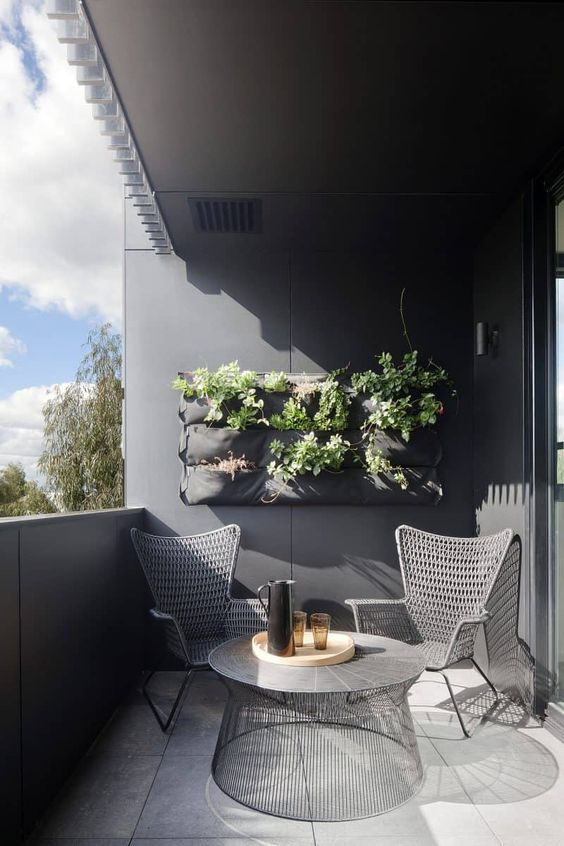 a stylish balcony with grey walls, woven chairs, a cool round table and potted greenery is a laconic and bold space to enjoy