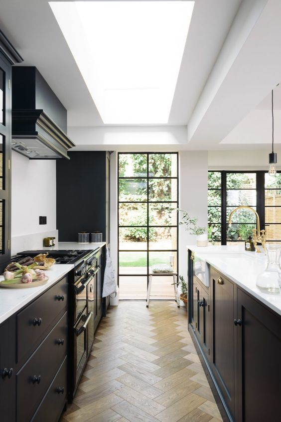 a stylish black kitchen with a large skylight and French windows with black frames, a black hood and a parquet floor is wow