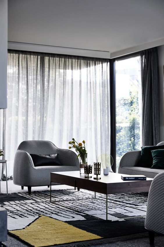 a stylish contemporary living room with curved furniture, a low coffee table and printed textiles and a large corner window
