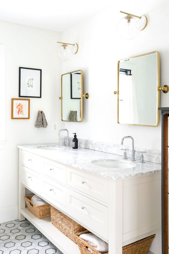 a stylish farmhouse bathroom in white, with a large vanity, mirrors in gold frames, gold sconces, chromatic faucets is a cool idea