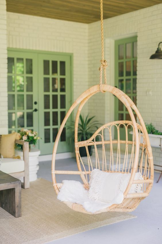 a stylish hanging rattan chair with pillows is a cool idea to style a rustic porch or another outdoor rustic space