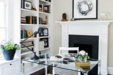 a stylish home office with built-in shelves, a glass desk, a fireplace behind it, a windowsill seat and potted plants and blooms
