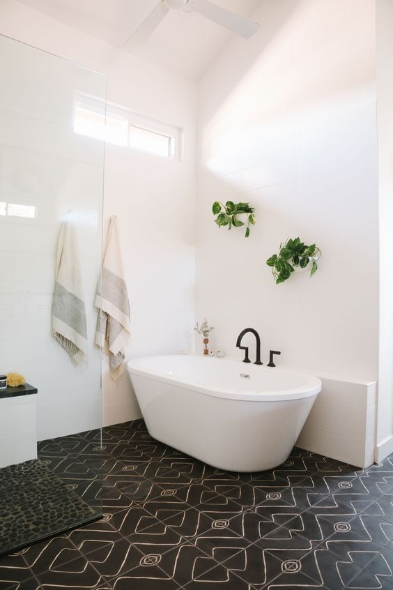 a stylish mid-century modern bathroom with white and black mosaic tiles, a tub, greenery and a black pebble rug