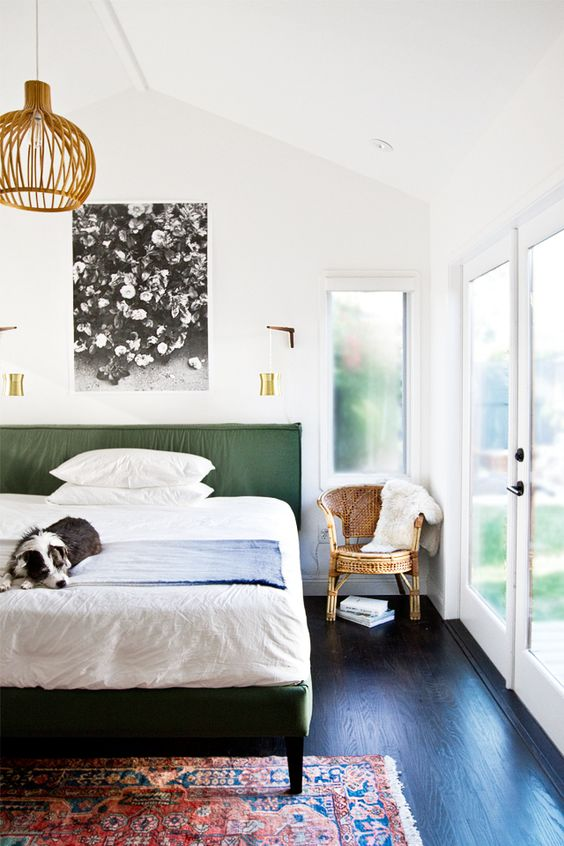 a stylish mid-century modern bedroom with a green upholstered bed, neutral bedding, a printed artwork, a woven pendant lamp and a rattan chair