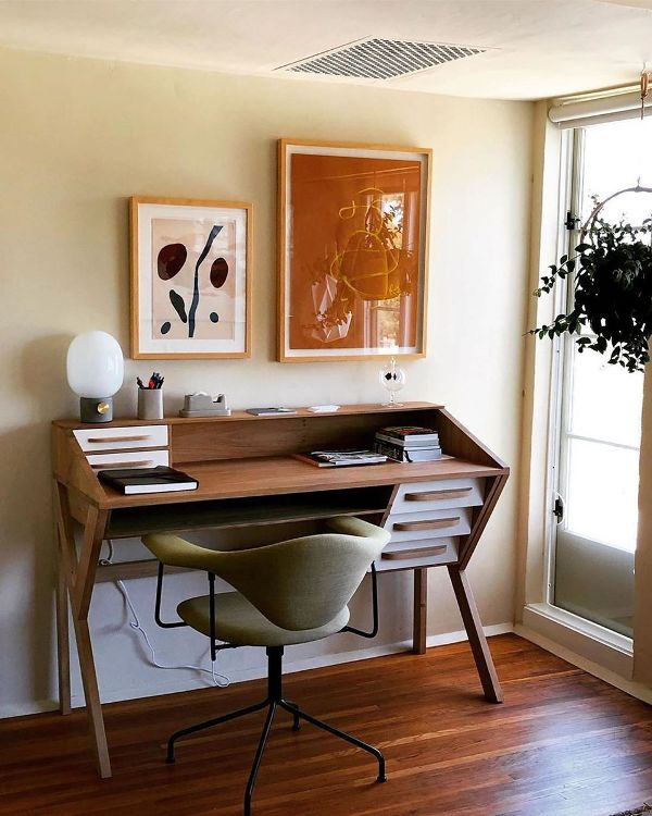 a stylish mid-century modern home office nook with a tiered desk, a green chair, a colorful gallery wall looks bold