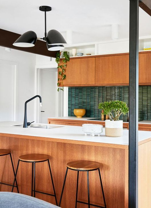 a stylish mid-century modern kitchen with light stained cabinets, white stone countertops, a green skinny tile backsplash, black fixtures and potted plants