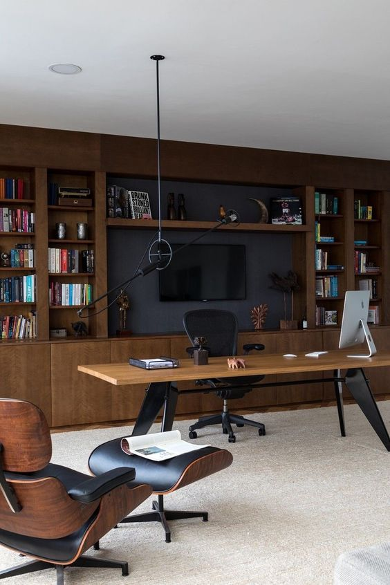 a stylish mid-century modern living room with a large storage unit of stained wood, a large desk, a leather chair and a cool pendant lamp