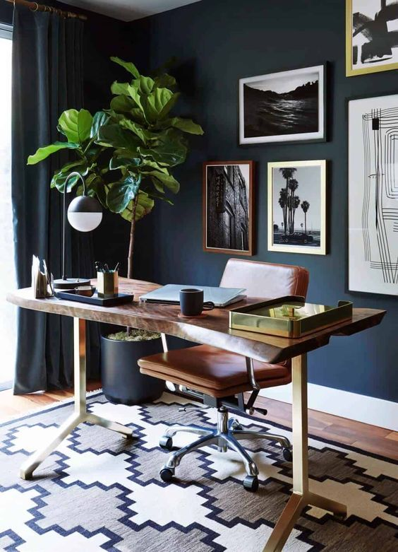 a stylish mid-century modern living room with navy walls, a rich-stained living edge desk, an amber leather chair, a potted tree and a gallery wall