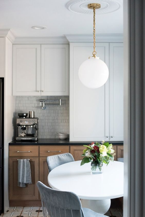 a stylish modern farmhouse kitchen with stained and white cabinets, a bubble lamp on a gold chain, chromatic applainces and handles on the cabients