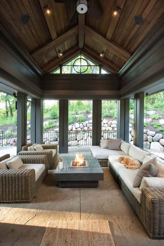 a stylish modern farmhouse screened porch with woven furniture, a portable fire pit, some lights is a lovely space to spend time
