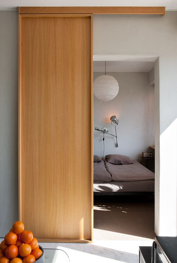 a stylish modern light-stained plywood sliding door is a beautiful solution for a modern or Scandinavian space and it looks eye-catching