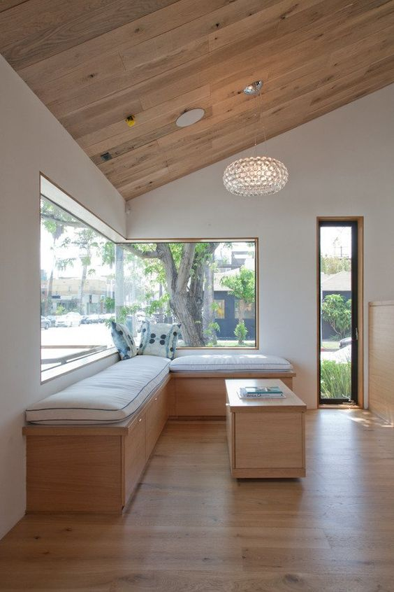a stylish modern space with a slanted ceiling, a large corner window and a built-in daybed and cushions plus a small coffee table