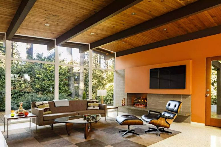 a super bright mid-century modern living room with a planked wood ceiling, an orange accent wall, a fireplace, a taupe sofa and a black leather chair