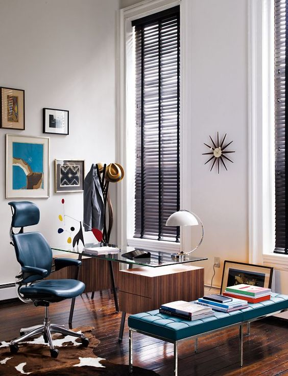 a super elegant mid-century modern home office with a wood and glass desk, a leather chair and a bench, a cowhide rug, a colorful gallery wall