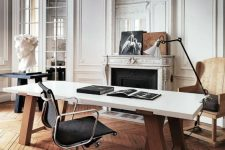 a super refined Parisian home office with molding on the walls and ceiling, an ornated fireplace, a desk, a black chair, a floor lamp and some art