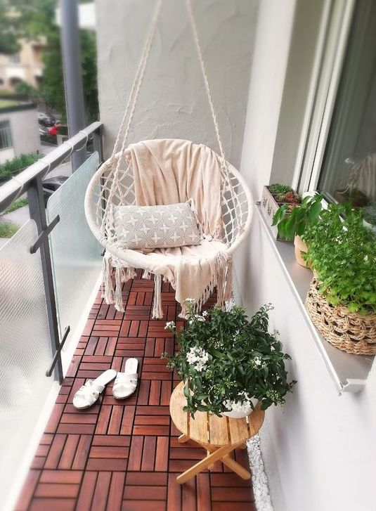 a tiny balcony with wood tiles, a lovely round hanging chair with pillows, a small folding table and potted greenery