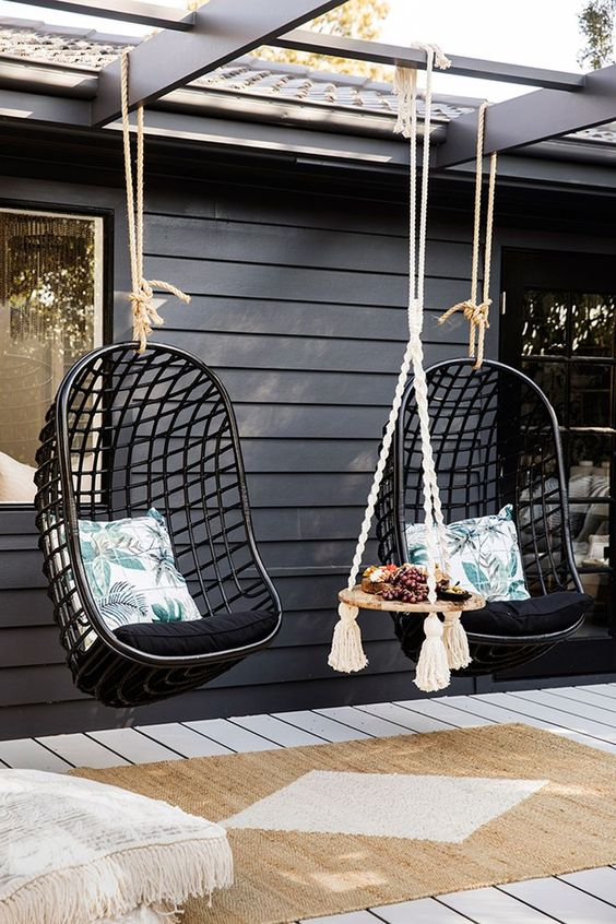 a tropical boho terrace with a deck, black rattan hanging chairs, printed cushions and pillows, a hanging side table and a jute rug